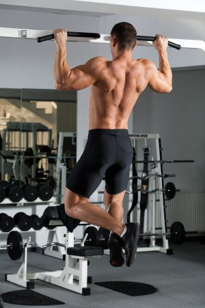 young body-builder training in the gym: back - Wide-Grip Front Pull-Up