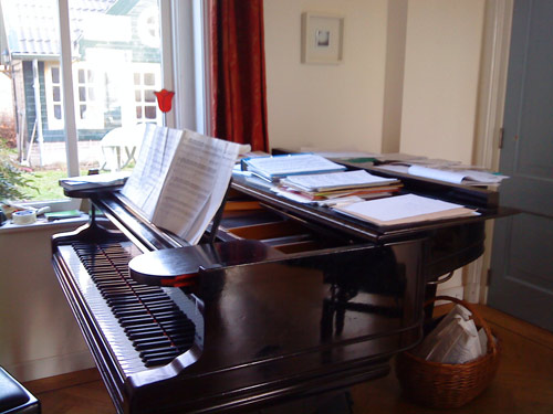 My piano with scores divided into piles: for French horn, cello, guitar, solo