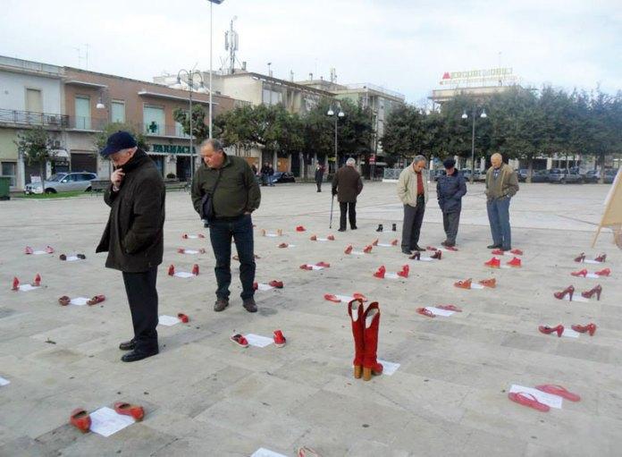 Scarpe rosse e storie su carta in piazza della Repubblica