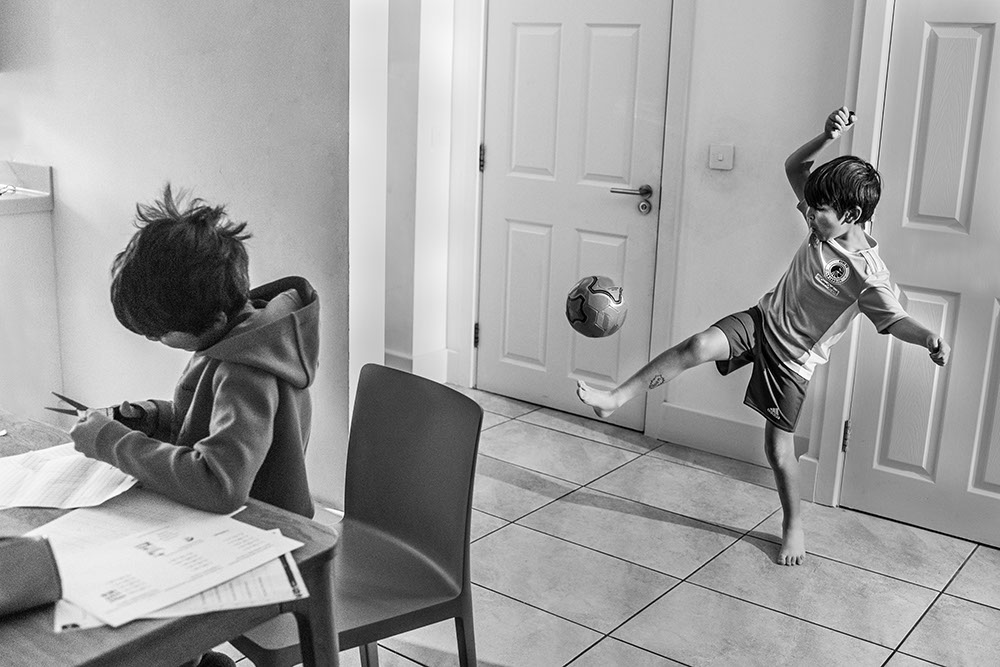 Siblings in the kitchen by family documentary photographer