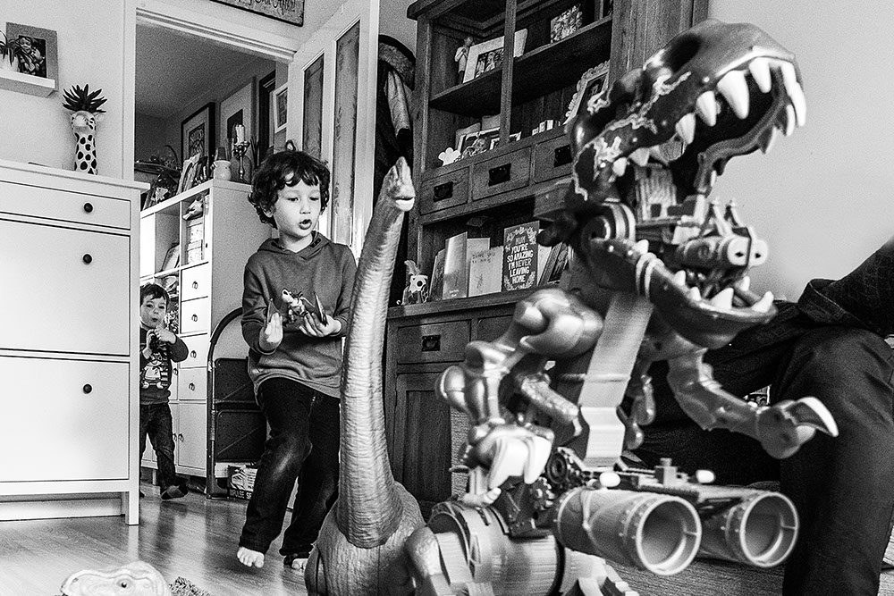 siblings playing with dinosaurs from family documentary photography session in London