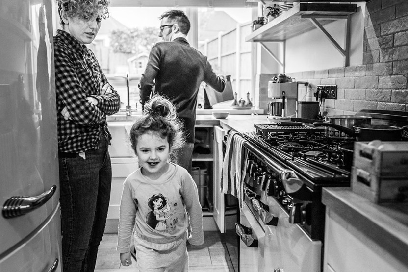 girl running from the kitchen with mum looking at her from family documentary photography session