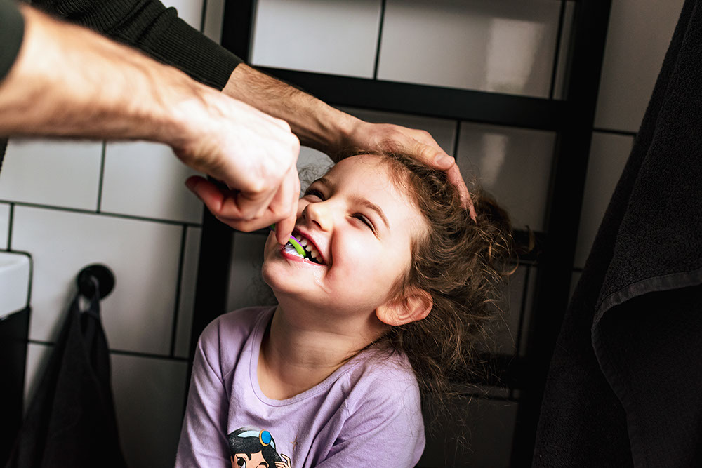 Dad brushing daughter's teeth from Documentary family photography in London