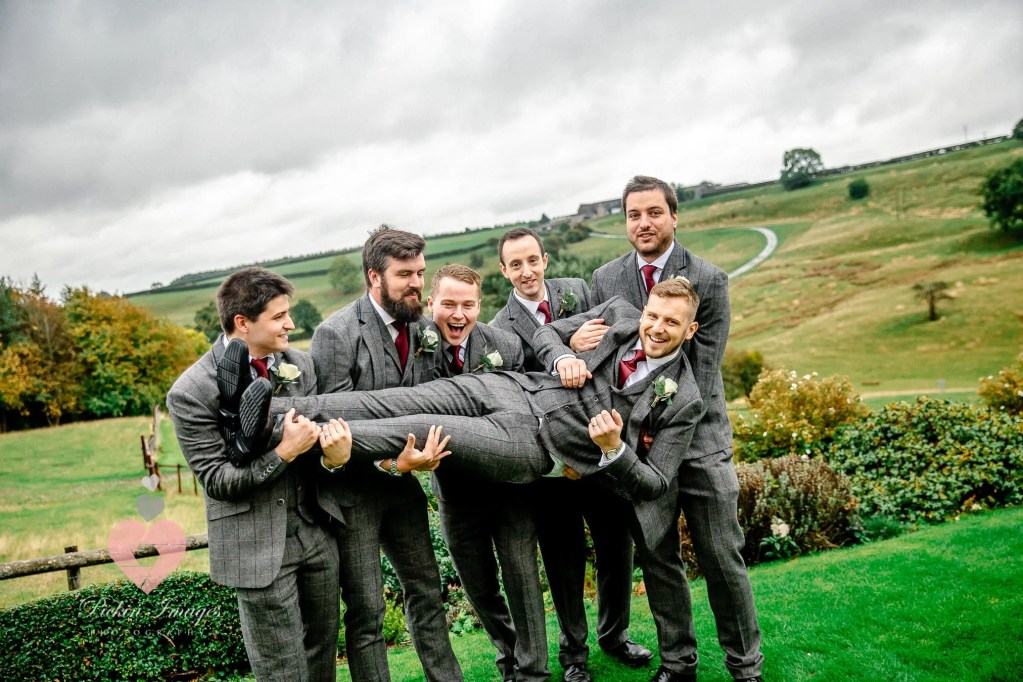Groomsmen lifting the groom up for photos.