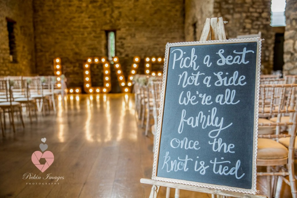 LOVE sign set up for the ceremony with seating plan.
