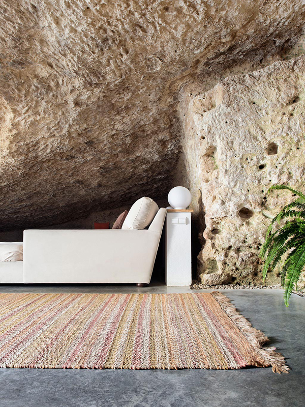 Rough cave walls and modern white furniture and woven rugs