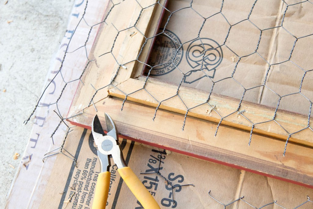 Trimming the chicken wire excess from the wooden frame