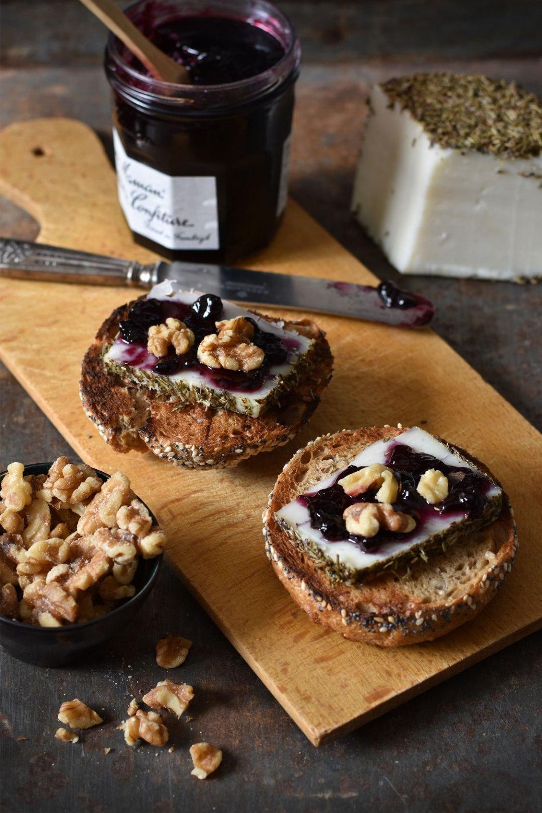 Gezonde toast met geitenkaas, tijm, bosbessenconfituur en walnoten.