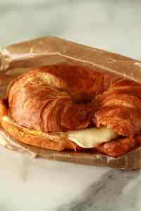 Ham, Egg and cheese in a croissant inside of a sandwich wrapper