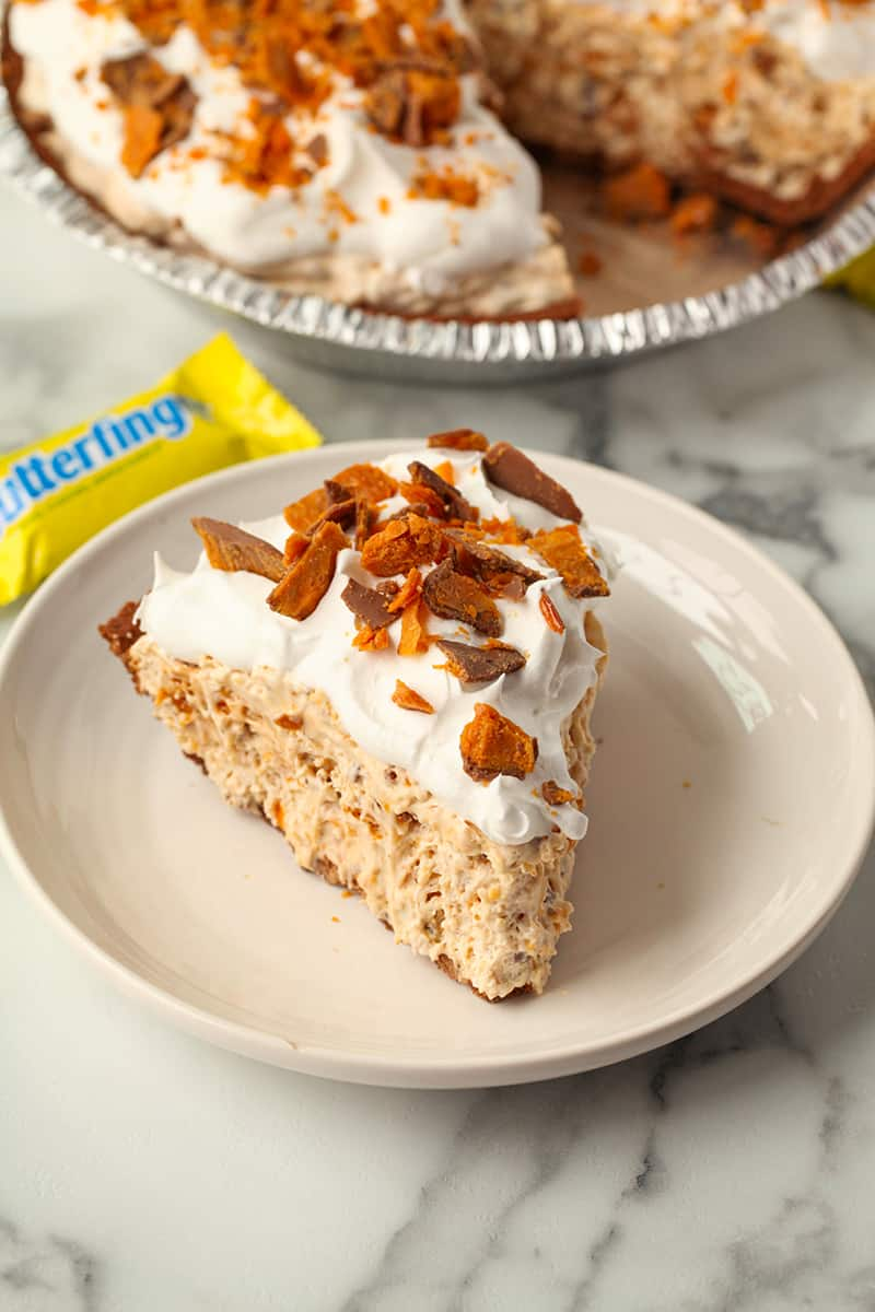 A slice of butterfinger pie with a miniature butterfinger candy bar behind it