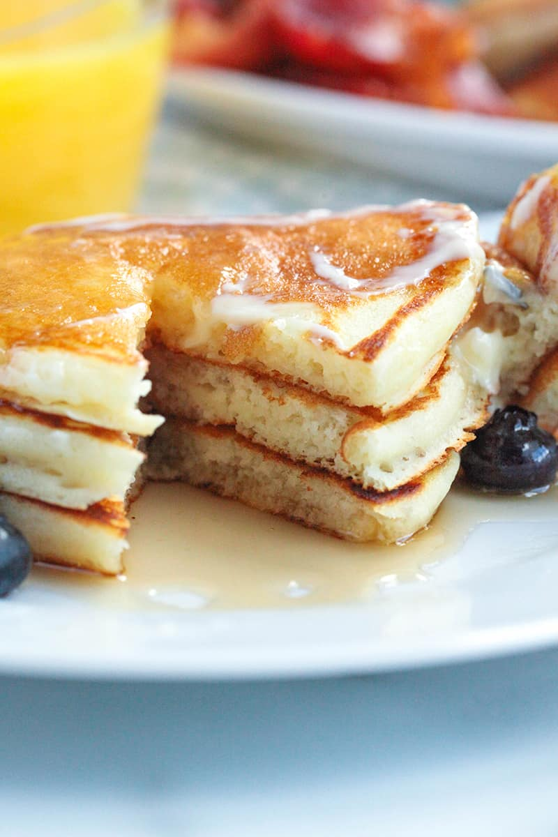 a stack of pancakes with a piece missing to show how fluffy they are