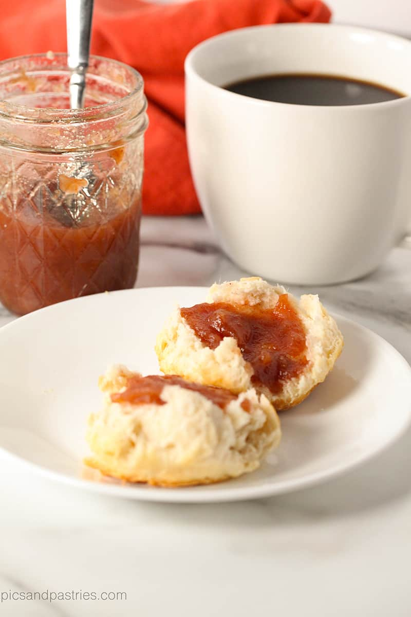jar of apple butter, cup of coffee and a biscuit with apple butter on it