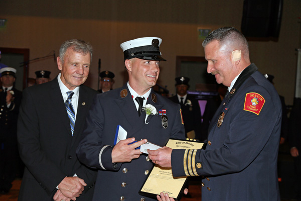 Firefighter Douglas Menard, with John F. Hasson, Interim Fire Commissioner, and Joseph E. Finn, Deputy Chief, at right.