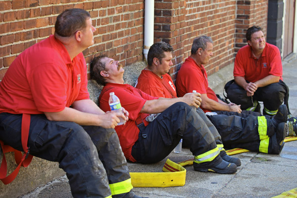 08/07/2015-Boston,MA. Boston firefighters from the Dudley Square fire house take a break from working the scene of a 3 alarm fire at 6 Waverly St. in Roxbury today. Staff photo by Mark Garfinkel
