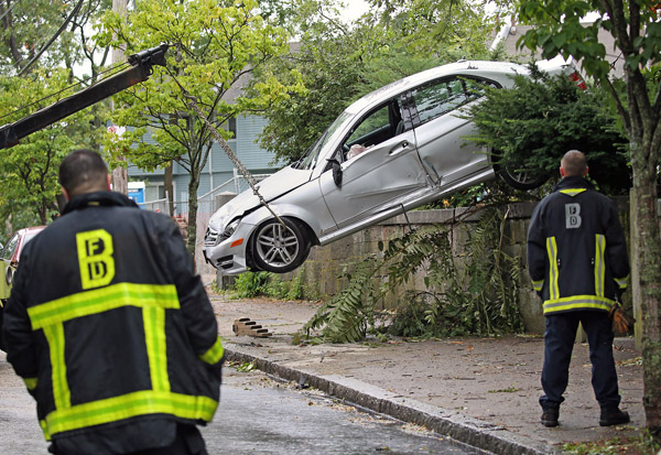 08/11/2015-Boston,MA. Boston firefighters watch as a car hangs off a driveway onto Roxbury's Cedar St. Tuesday afternoon. No serious injuries were reported.
