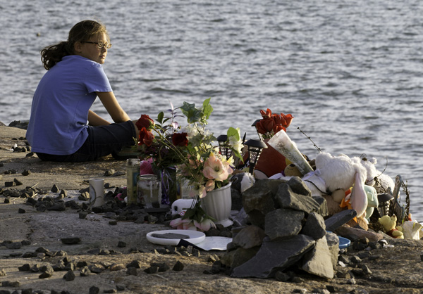08/29//15-Boston,MA Syla Rapaglia, age 11 years, sits at the makeshift memorial for the child known as Baby Doe, whose body was found at Deer Island on June 25. Skla's mother organized the 2nd vigil for the missing child, held tonight.