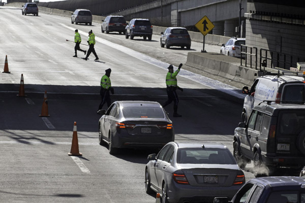 02/12/2016-Boston,MA. State Police investigators are seen on Route 93 Southbound, just outside of the O'Neill Tunnel, near the spot where a manhole resided before coming loose and eventually flying into a car's windshield killing a woman during Friday morning's commute. Staff photo by Mark Garfinkel