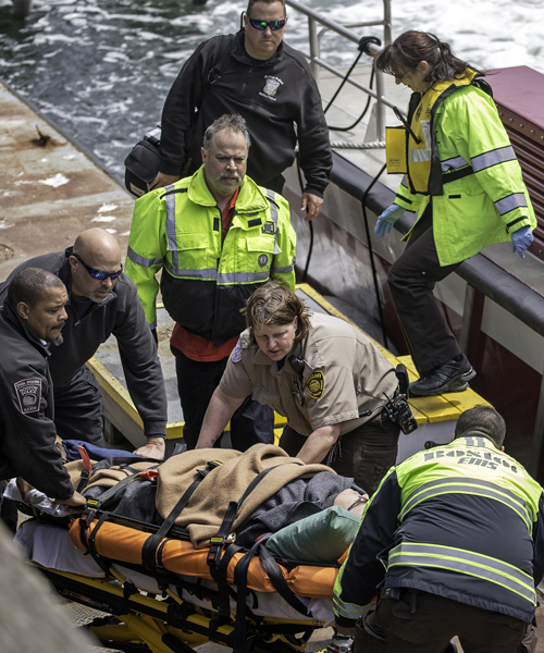 04/29/2016-Boston,MA. A man suffering from an ailment, who had been aboard the oil tanker Hugli Spirit, is seen on a gurney after Boston EMS, fire and police Marine Unit officials, along with the Coast Guard and Environmental police took him off the ship, to a dock, and then to a waiting ambulance. Staff Photo by Mark Garfinkel