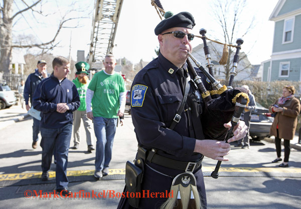 04/09/2016-Boston,MA. Boston Police officer Tim Horan, a Pipe Sergeant in the Boston Police Gaelic Column of Pipes and Drums, escorts Mayor Martin J. Walsh, to the annual Shamrock Shootout Street Hockey Tournament on Temple St. in the West Roxbury section of the city, Saturday morning. Staff photo by Mark Garfinkel