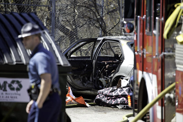 04/27/2016-West Roxbury,MA. A Massachusetts state trooper is seen near the remains of a car that was involved in a long-duration police pursuit that began in Walpole, and ended in West Roxbury. The car caught fire at the 1400 block of VFW Parkway. Staff Photo by Mark Garfinkel