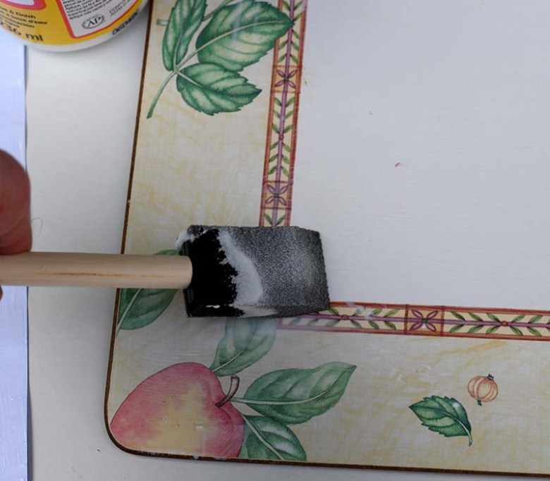 Applying decoupage glue to placemat