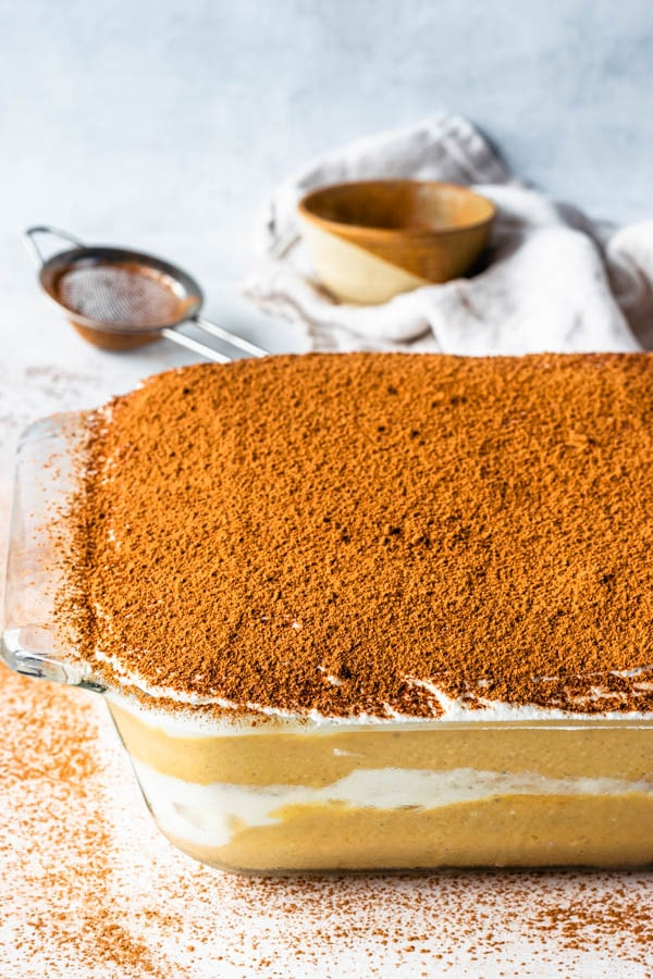 Pumpkin tiramisu dusted with cocoa powder in a glass dish