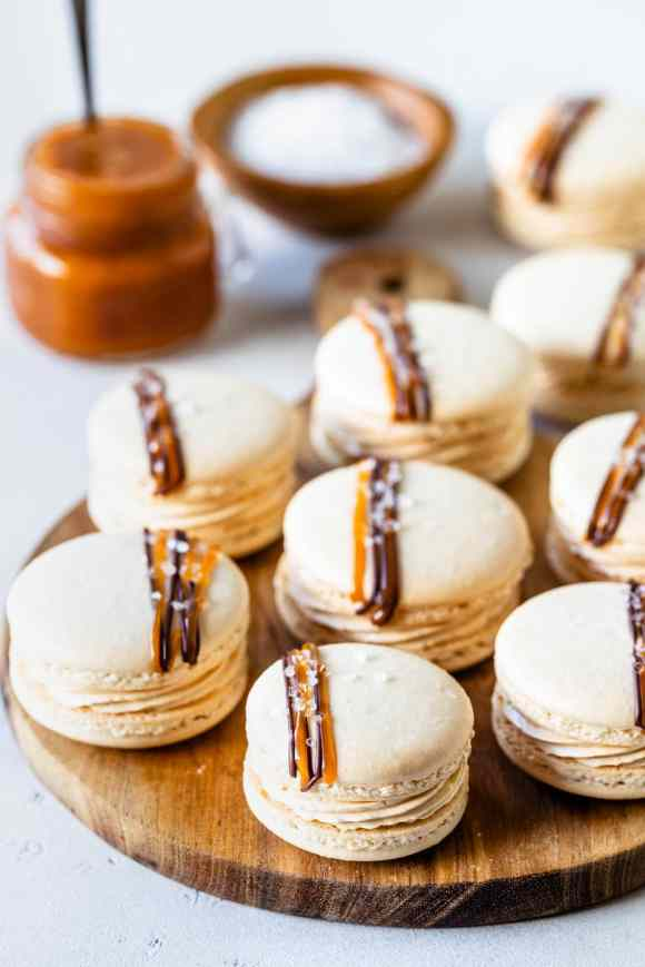Salted Caramel Macarons filled with buttercream and topped with a drizzle of salted caramel and chocolate