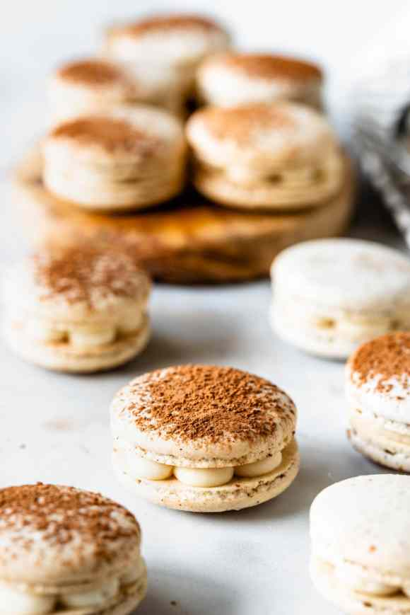 Tiramisu macarons filled with mascarpone frosting, dusted with cocoa powder