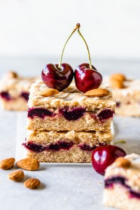 Almond Cherry Bars stacked on top of each other topped with two cherries