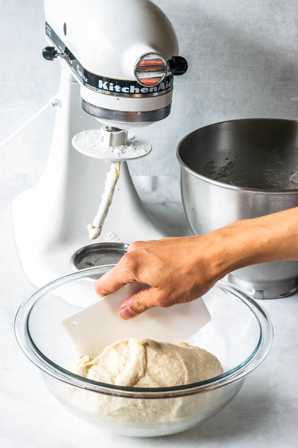 vegan donut dough being placed in a lightly oiled bowl