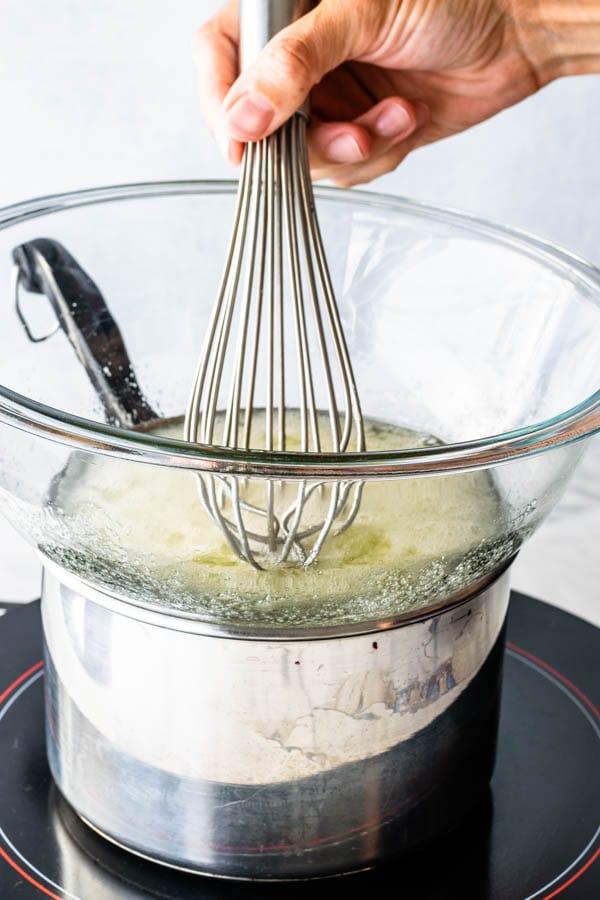 whisking egg whites and sugar over double boiler