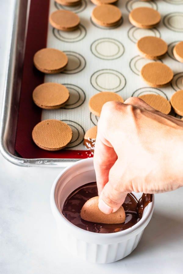 dipping macaron shells in chocolate