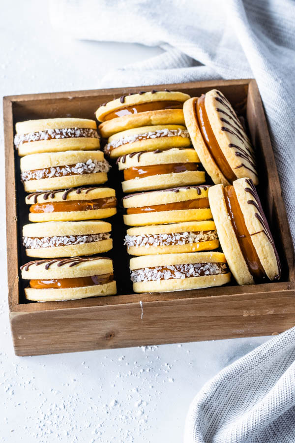 Alfajor Cookies filled with dulce de leche drizzled with melted chocolate