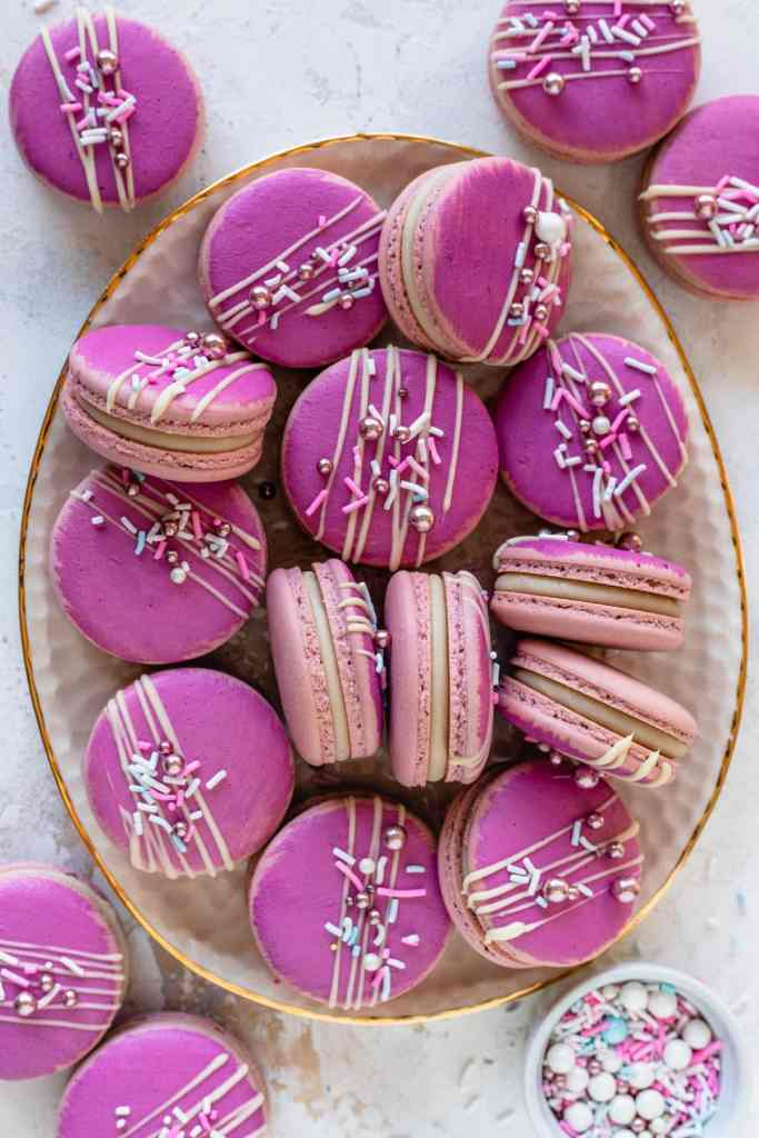 Champagne Macarons pink macarons topped with a drizzle of white chocolate and sprinkles.