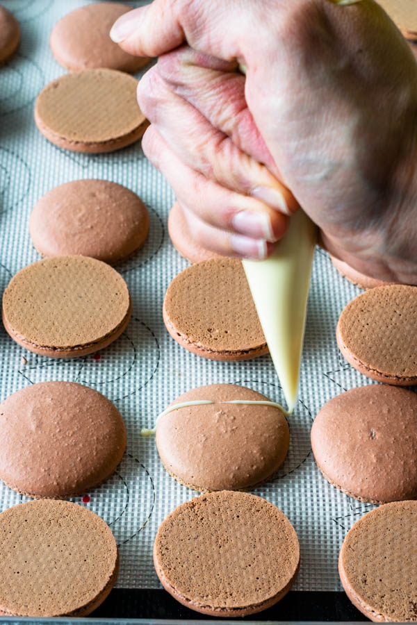 drizzling white chocolate on top of macaron shells