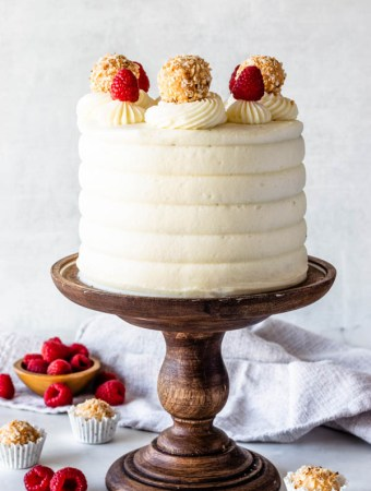 Raspberry Coconut Cake topped with raspberries and coconut fudge truffles