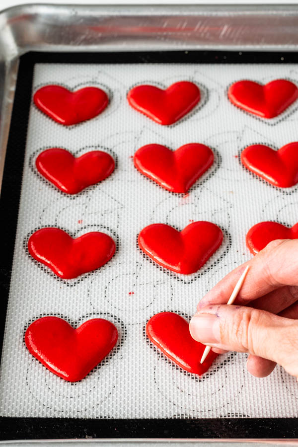 using a toothpick to spread the batter of the heart shaped macarons