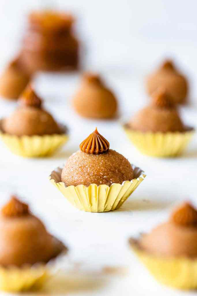 dulce de leche truffles as known as churros brigadeiros in small golden paper cups.