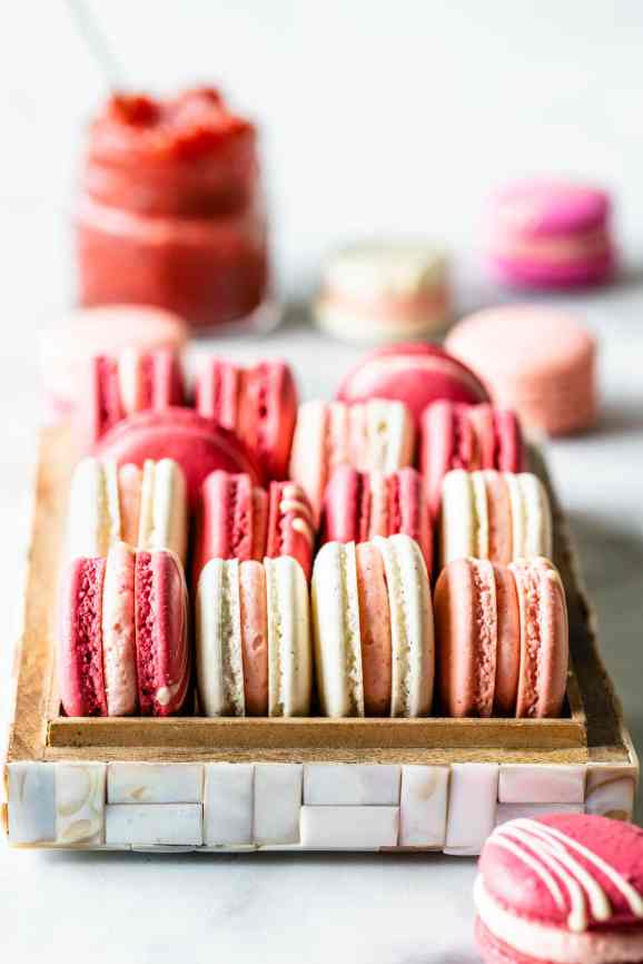 Pink, white, and dark pink strawberry rhubarb macarons in a box, with jam in the top left corner