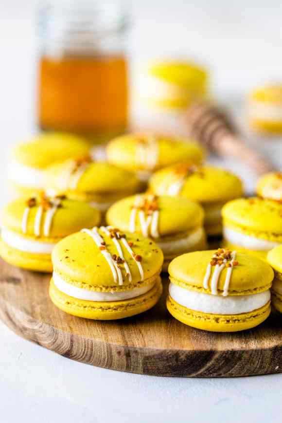 yellow Macarons topped with bee pollen on a wooden board with a jar of honey on the back