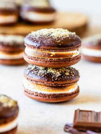 S'mores Macarons dipped in chocolate topped with graham cracker crumbs filled with toasted marshmallow