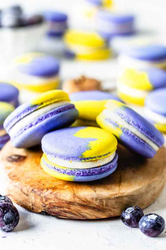 purple and yellow vegan macarons filled with buttercream on top of a wooden board with blueberries around and on the back a jar of blueberry jam and half of a lemon