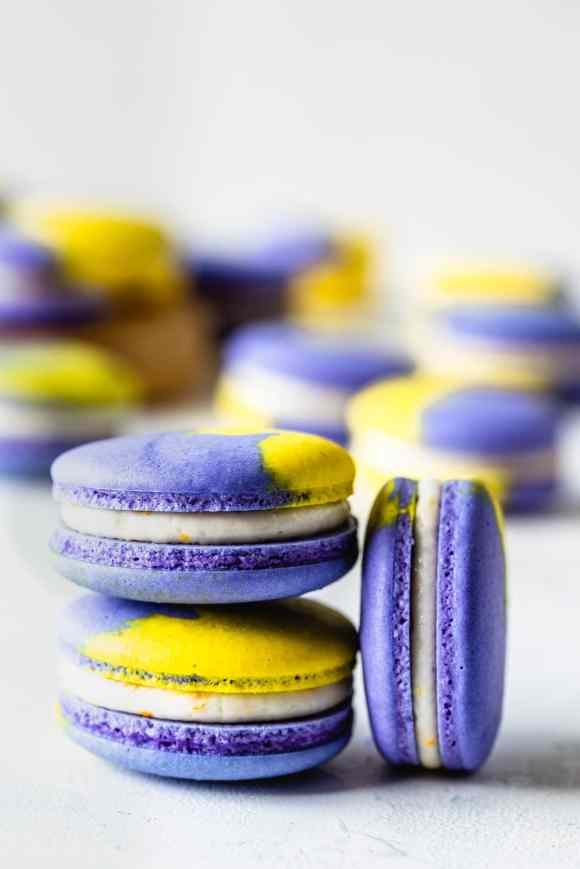 Vegan Lemon Blueberry Macarons purple and yellow shells filled with lemon buttercream, two macarons stacked on top of the other and one macaron on the side