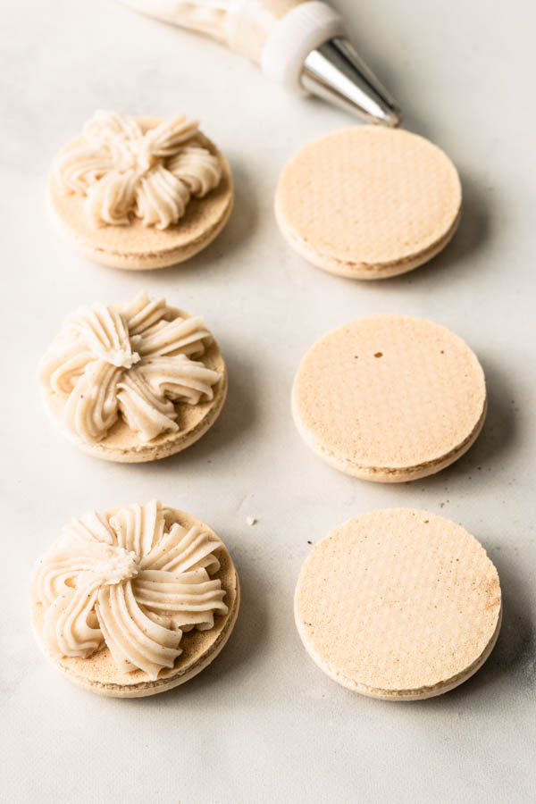 macaron shells with eggnog filling piped in the middle with a fancy piping.