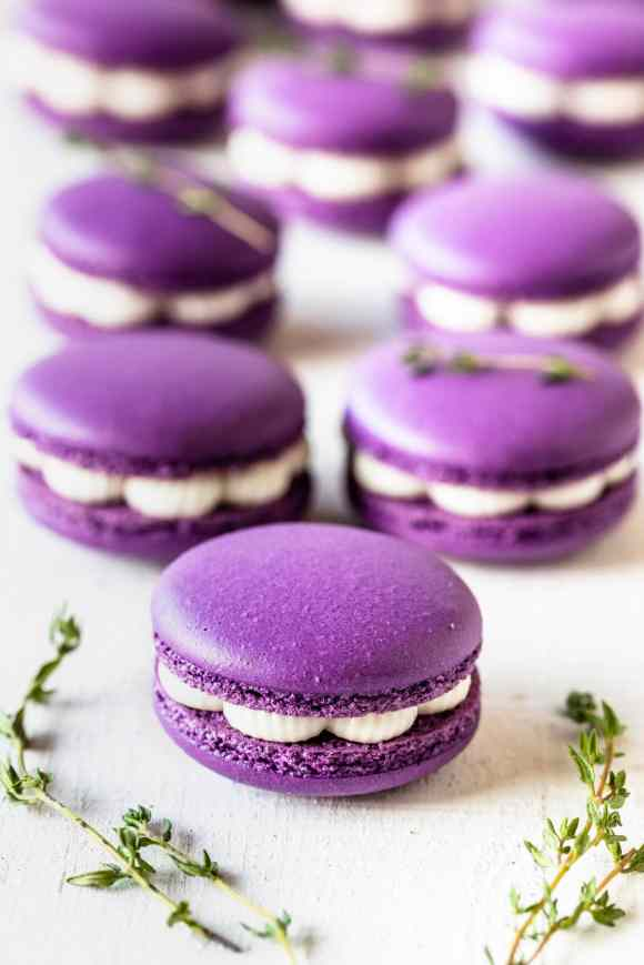 purple macarons filled with fig jam and buttercream, with thyme as a garnish on top.