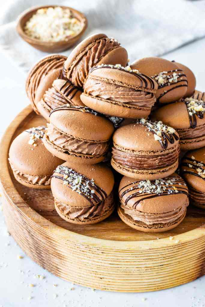 chocolate macaron shells filled with nutella buttercream on top of a round wooden stand.