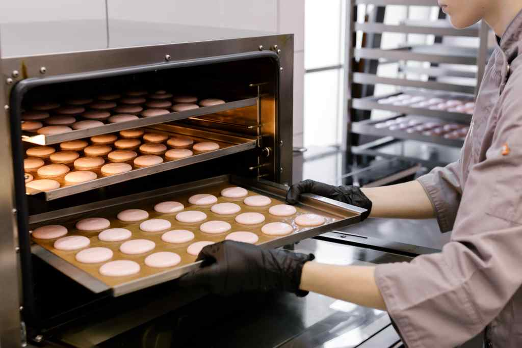 person putting a tray of macarons in the oven.