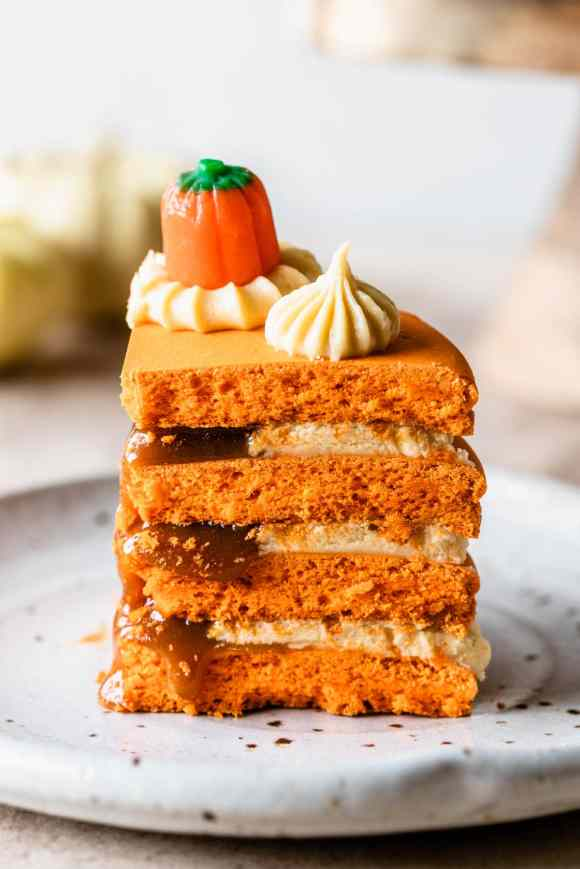 slice of macaron cake showing the filling of caramel dripping.