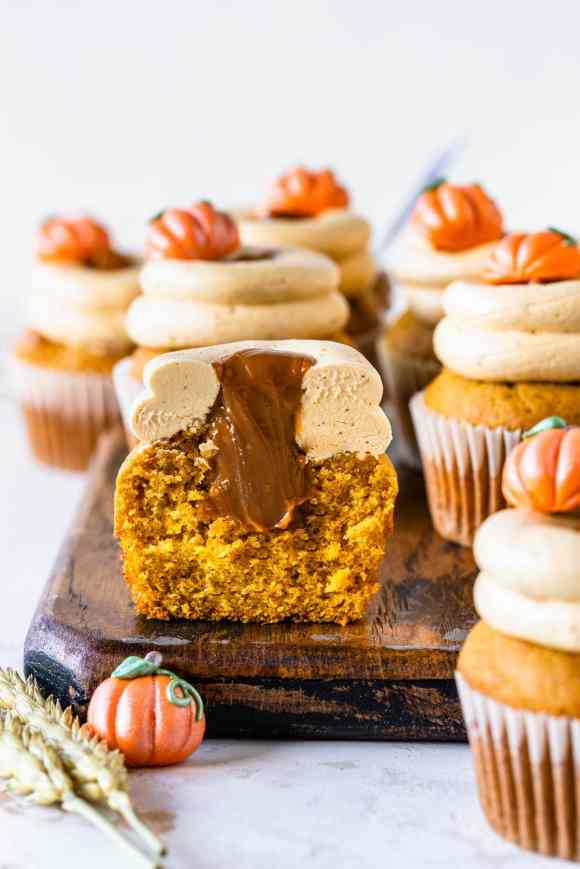 pumpkin cupcakes filled with dulce de leche cut in half showing the filling.