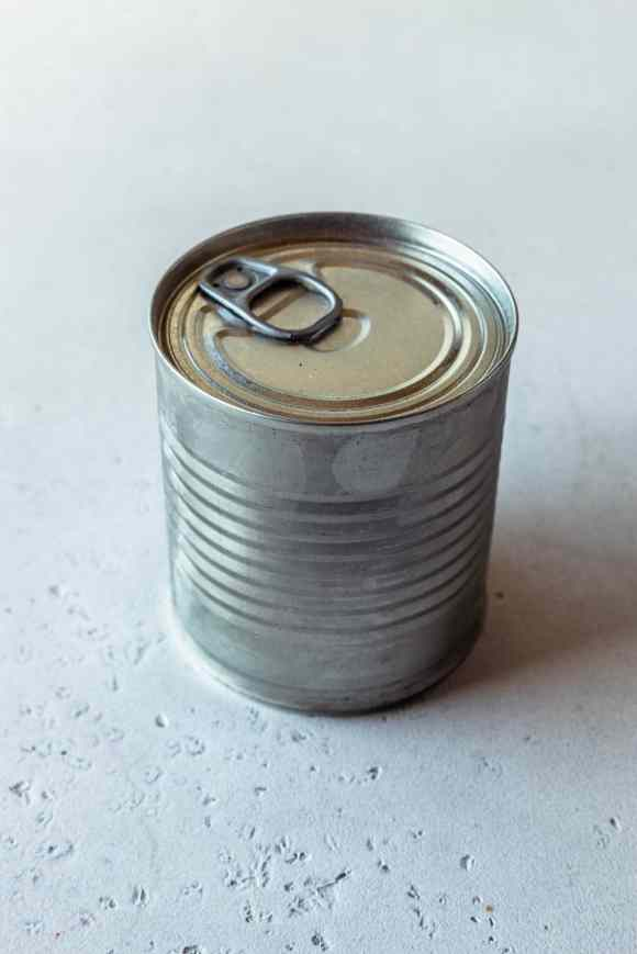 sealed can of condensed milk without a label.